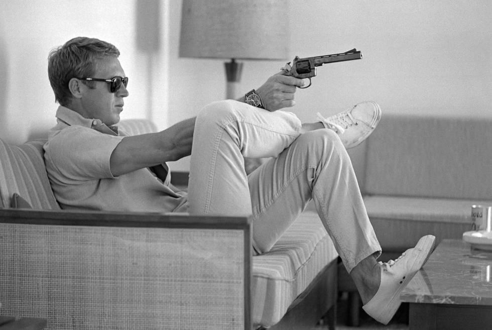 Steve McQueen, sentado no sofá de sua casa em Palm Springs (Califórnia) com uma pistola na mão, em maio de 1963.