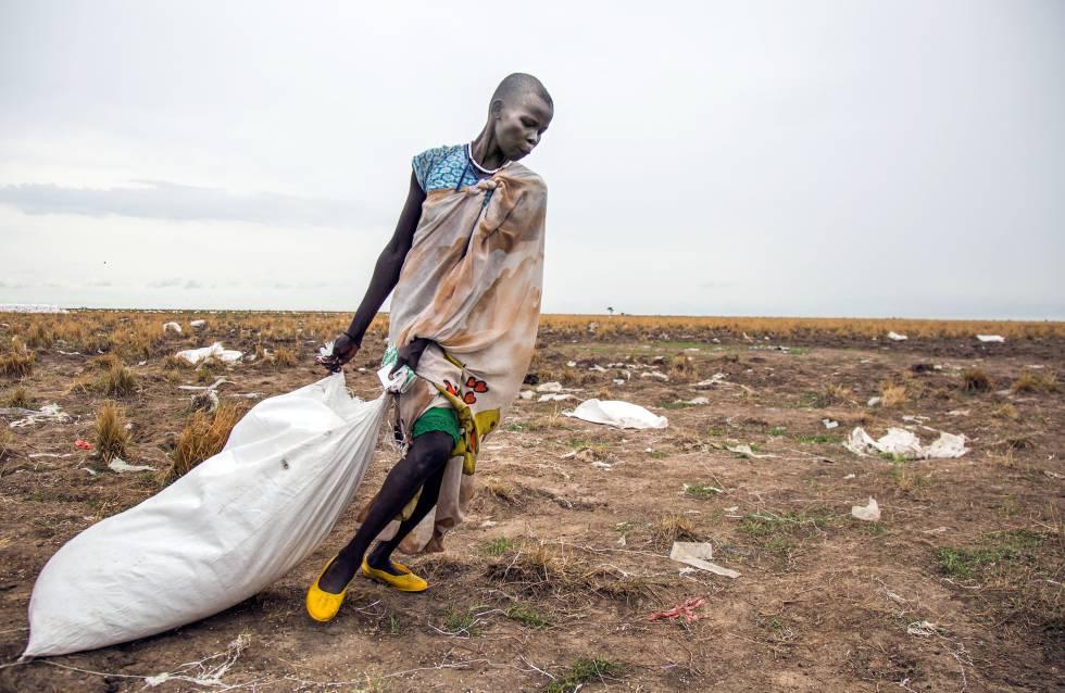 Mulher arrasta saco de comida jogado do alto pelo Programa Mundial de Alimentos no Sudão do Sul