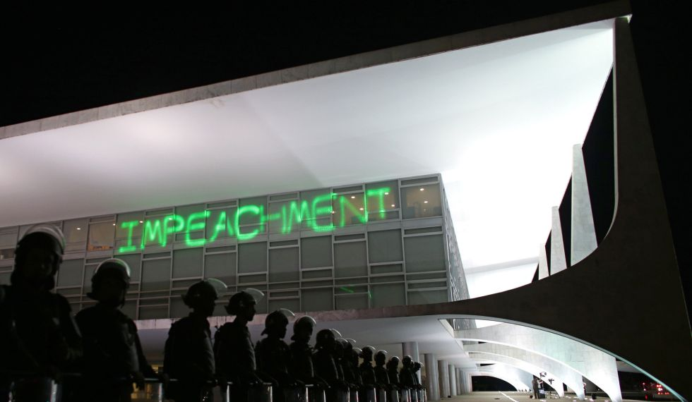 Manifestantes projetam a palavra impeachment no Palácio do Planalto.