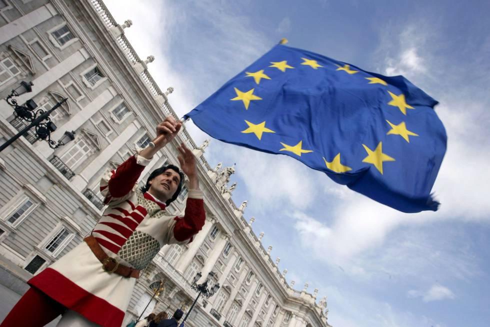 """Um membro do grupo italiano """"Sbandieratori dei Siena"""" enquanto sustenta uma bandeira da União Europeia  em frente ao Palácio Real em Madri."""