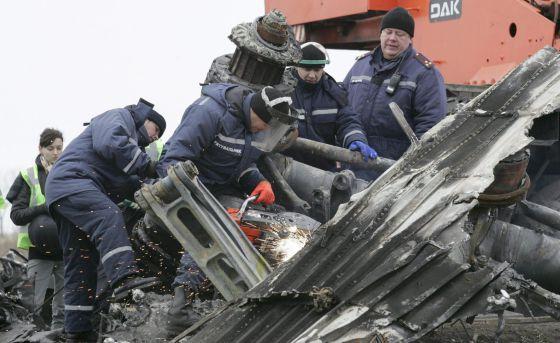 Trabalhadores retiram restos da fuselagem do avião em Grabovo.
