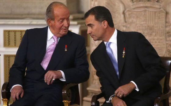 Dom Juan Carlos e dom Felipe no início do ato de assinatura da abdicação.