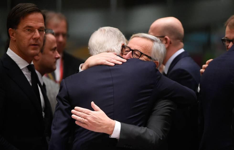 Juncker e Barnier s abraçam na cúpula de Bruxelas, neste domingo.