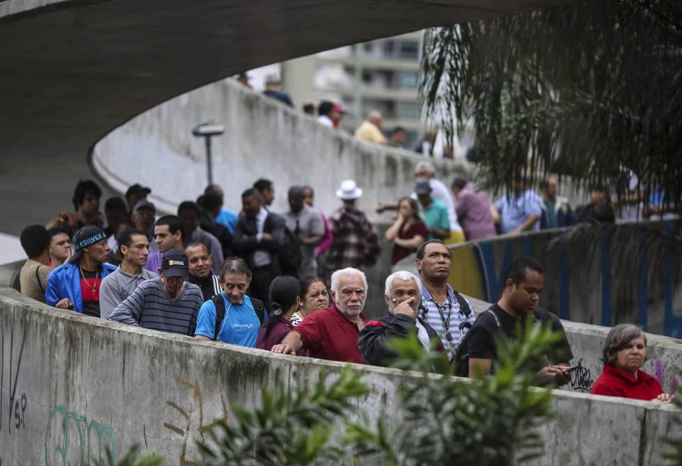 Eleitores fazem fila na favela da Rocinha para votar para prefeito e vereador no Rio de Janeiro. Capital fluminense tem disputa apertada para a prefeitura.