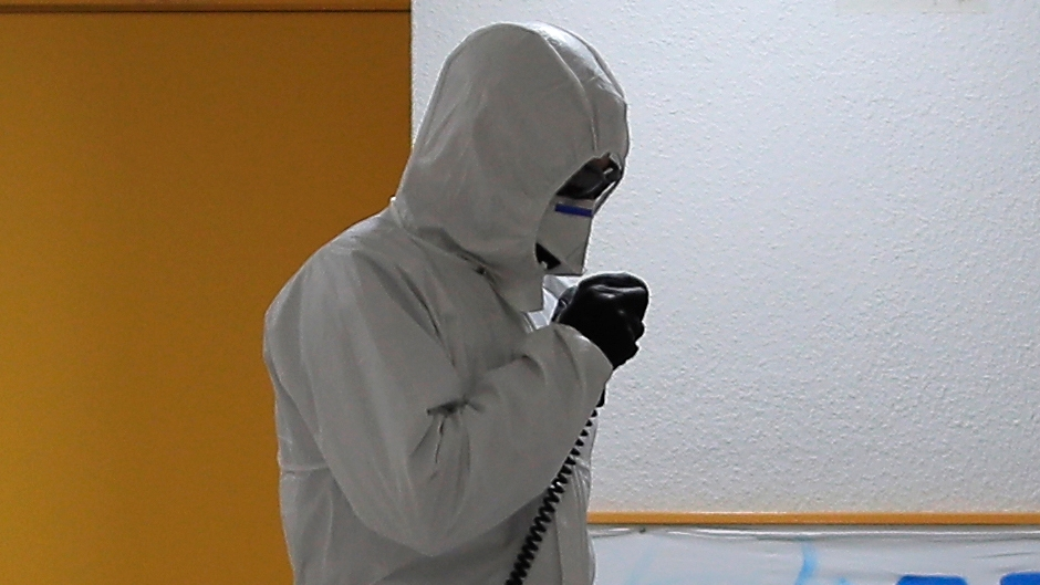 """A member of the UME (Emergency Army Unit) wearing a wearing a protective suit to protect against coronavirus disinfects next to a banner reading in Spanish: """"I will resist, Thanks everybody"""" at a nursing home in Madrid, Spain, Tuesday, March 31, 2020. The new coronavirus causes mild or moderate symptoms for most people, but for some, especially older adults and people with existing health problems, it can cause more severe illness or death. (AP Photo/Manu Fernandez)"""