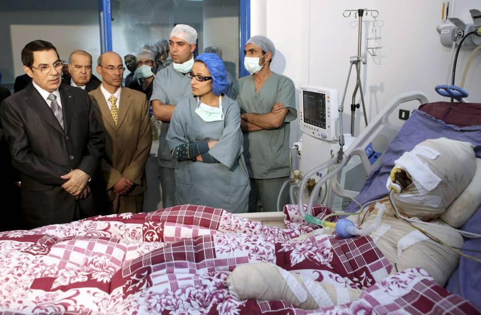 O então presidente tunisiano Ben Ali (à esquerda) visita no hospital o jovem que se imolou em 17 de dezembro de 2011.