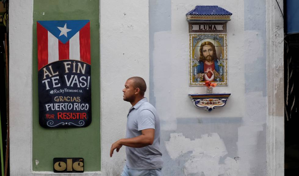 Um homem caminha junto a um cartaz que comemora a demissão do governador Ricardo Rosselló.