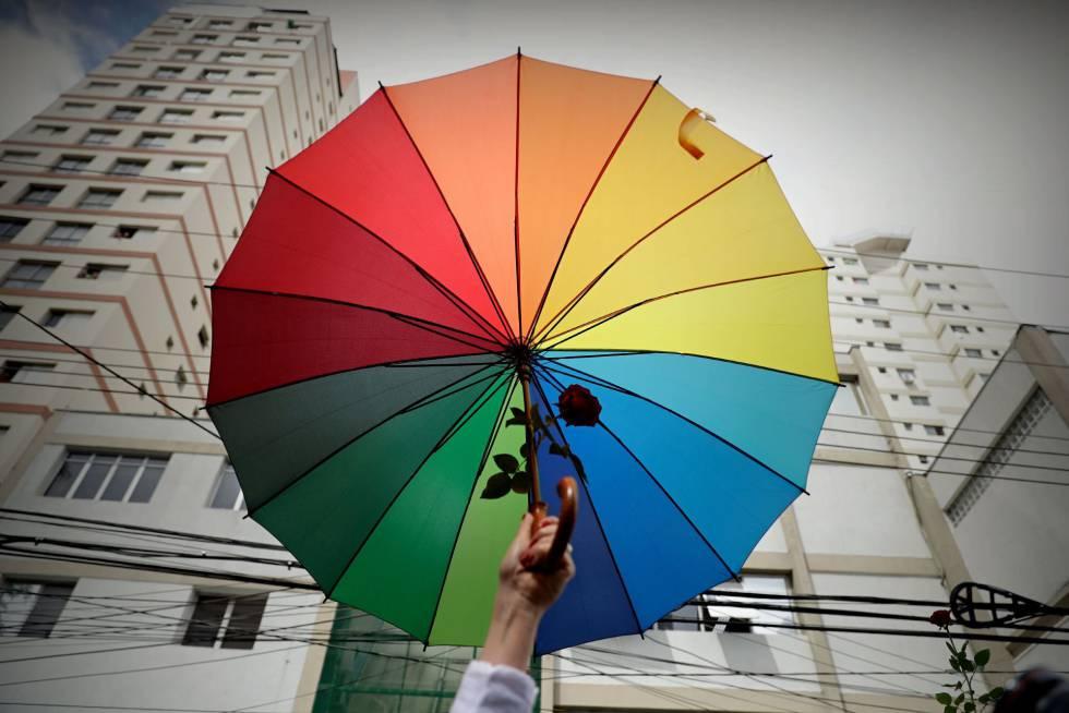 Manifestante defende bandeira LGBT, em frente a um colégio eleitoral de São Paulo