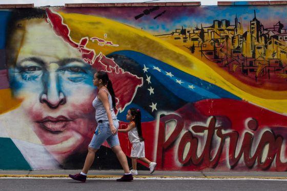 Mulher caminha em frente a um mural de Chávez.