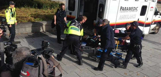 Policiais e paramédicos socorrem homem ferido no tiroteio.