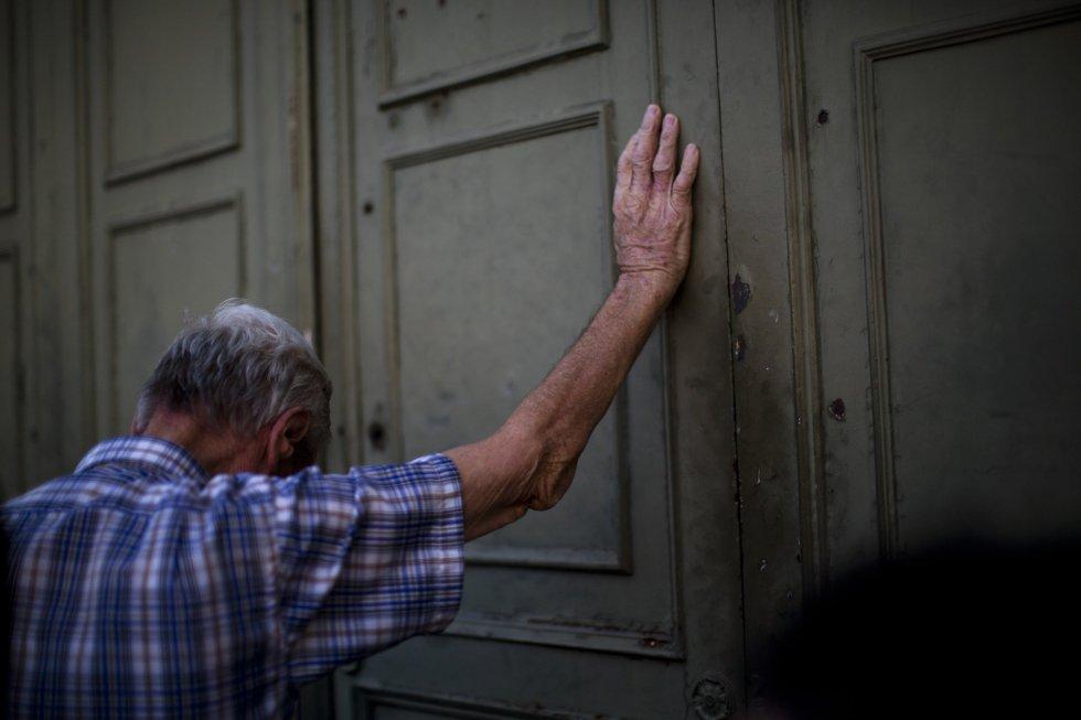 Um pensionista se apoia na porta principal do Banco Nacional da Grécia enquanto espera para retirar um máximo de 120 euros para a semana, em Atenas.