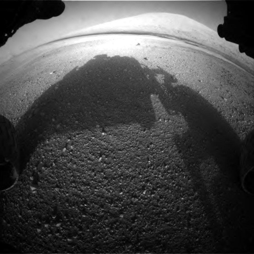 A primeira imagem da câmera frontal do rover, usada para detectar obstáculos durante a travessia. é possível ver ao longe o monte central da cratera Gale, Aeolis Mons, objetivo primordial para das investigações do Curiosity.