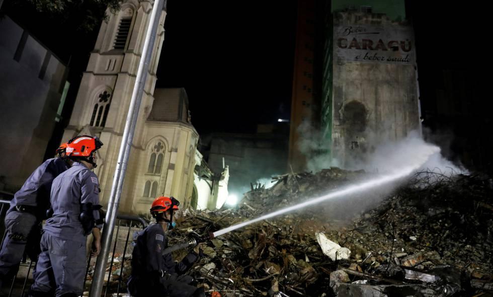 Bombeiros trabalham nos escombros do prédio desabado.