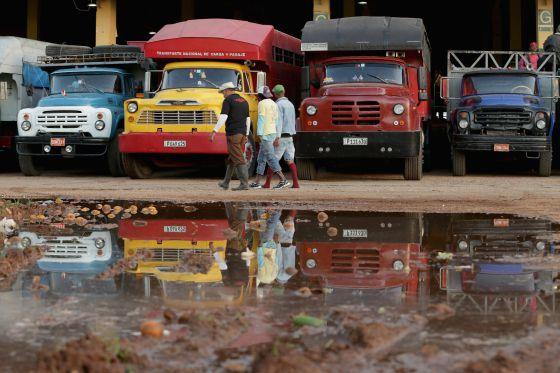 Um grupo de trabalhadores passa diante de caminhões em Havana.