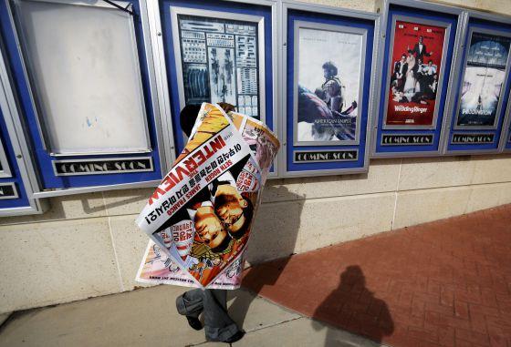 Funcionário retira cartazes de A Entrevista de um cinema em Atlanta.