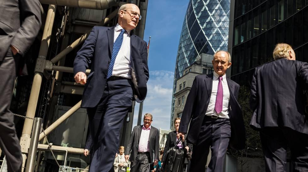 Funcionários caminhando por rua do distrito financeiro de Londres.