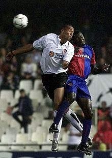 El valencianista Carew (izda.) salta con el jugador del Basilea Atouba.