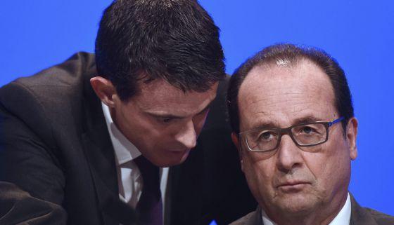 O presidente francês, François Hollande (direita), escuta a seu primeiro-ministro Manuel Valls, ontem em um encontro com prefeitos em Paris.