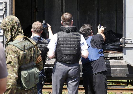 Inspetores da OSCE fotografam os corpos na estação de Torez.