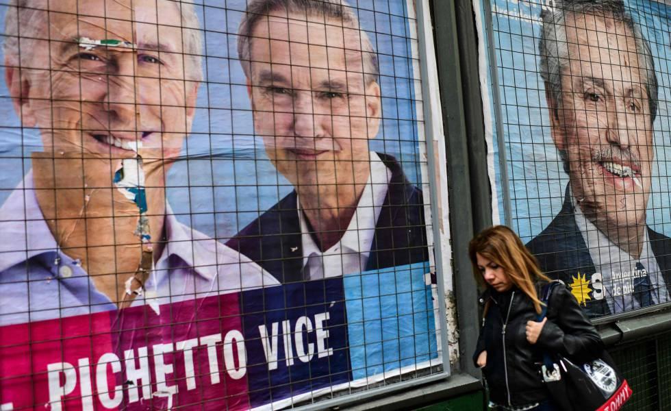 Mulher passa diante de cartazes de propaganda de Mauricio Macri e Alberto Fernández em uma rua de Buenos Aires.