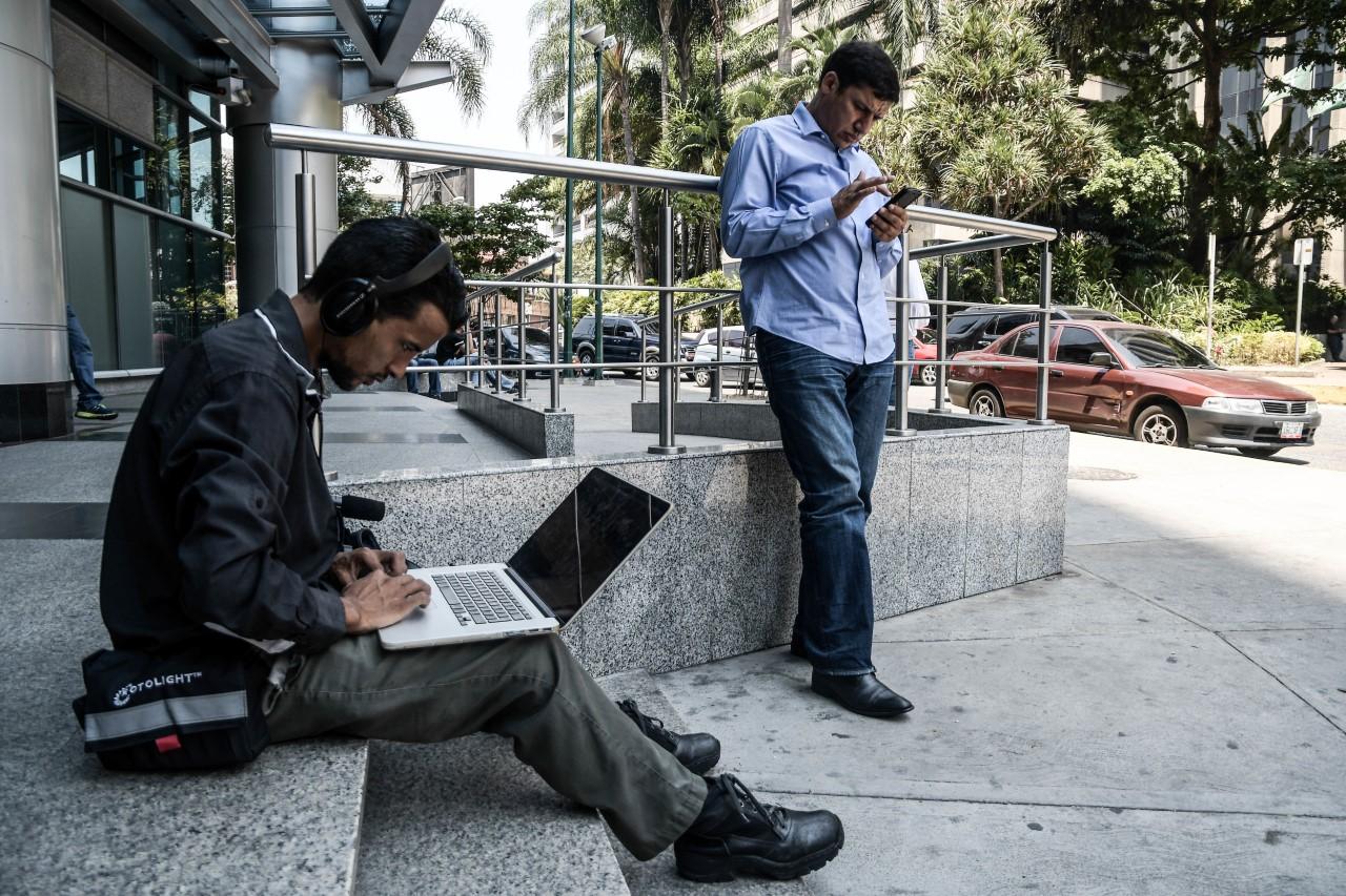Dos personas tratan de conectarse a Internet en Caracas durante un apagón en abril de 2019.