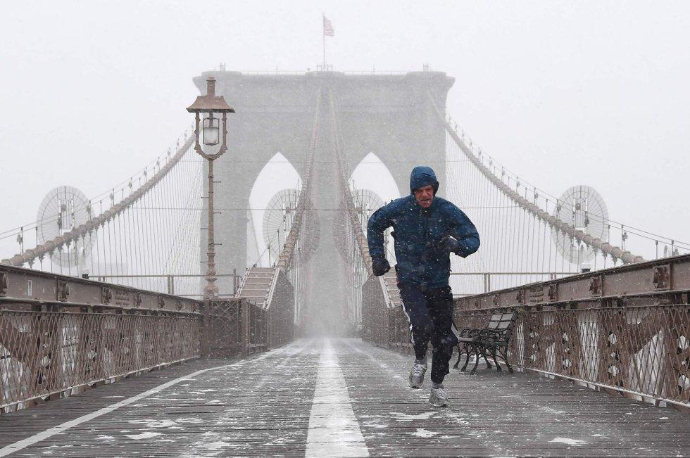 """Um homem corre pela ponte de Brooklyn em Nova York nesta quinta-feira. Toda a Costa Leste dos Estados Unidos se prepara para uma tempestade de inverno que poderia alcançar proporções históricas. O Estado de Nova York declarou estado de emergência na zona sul de seu território ante a chegada do poderoso fenômeno meteorológico. A partir desta quinta-feira até o fim da semana, o temporal subirá pelo noroeste, e se prevê que uma abrupta queda da pressão atmosférica a transforme numa """"bomba ciclônica"""" – ou ciclogênese explosiva – que soma ao frio fortes rajadas de vento, desencadeando perigosas tempestades de neve."""