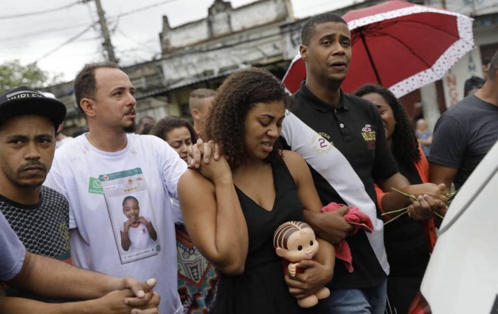 Vanessa Francisco Sales leva uma boneca que foi de sua filha, Ágatha Félix. Está de mãos dadas com Adegilson Félix, seu marido e pai da menina, durante o velório.
