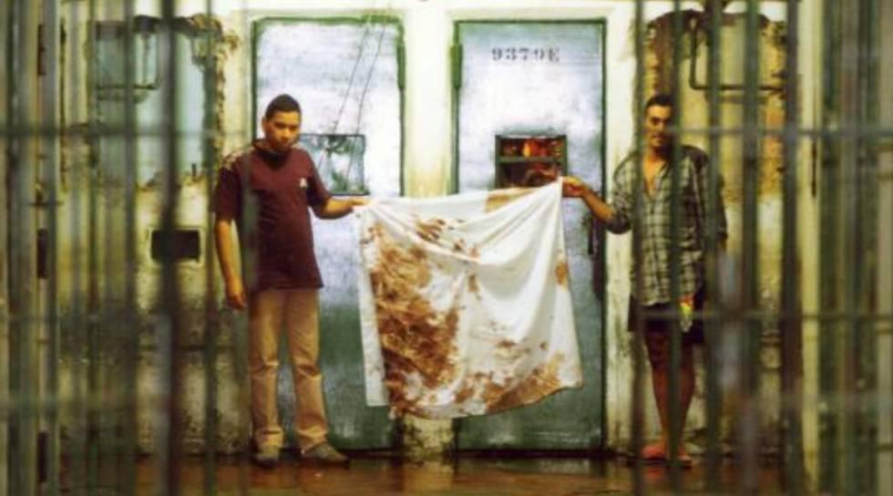 Detentos mostram pano sujo de sangue no Carandiru, em outubro de 1992.