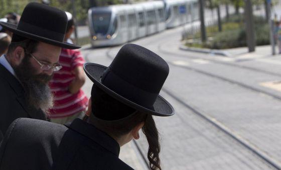 Pessoas esperam o bonde em Jerusalém.