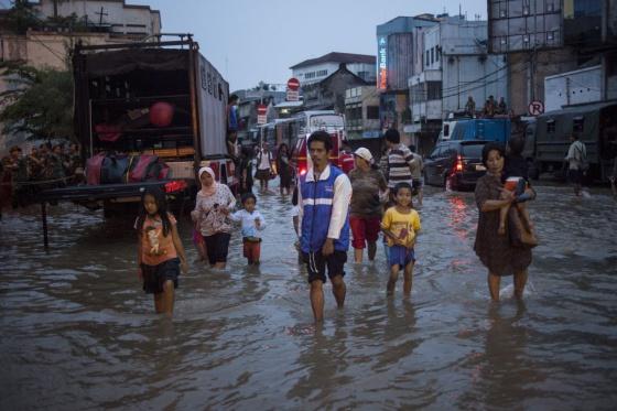 Pessoas de Jacarta caminham por uma rua inundada.
