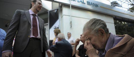 Um gerente do Banco Nacional da Grécia em Tessalônica explica a situação a um grupo de pensionistas que espera do lado de fora da agência.