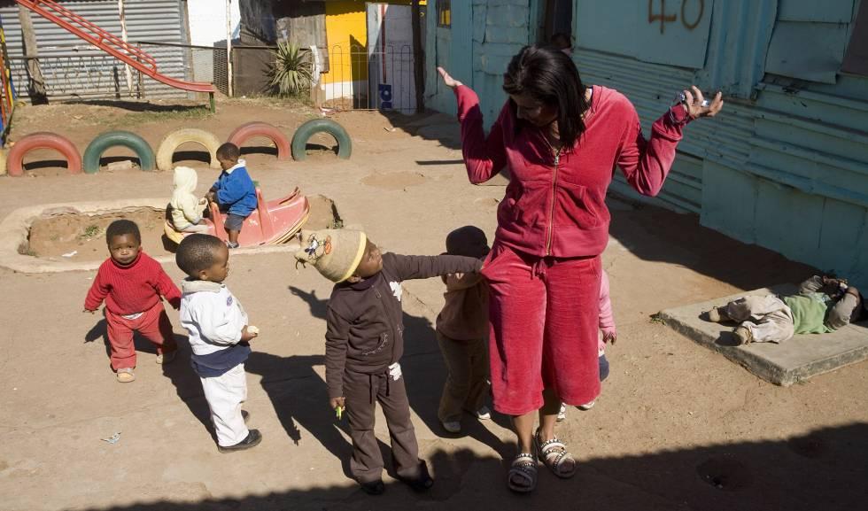 Crianças xeretam os bolsos de uma visitante em um jardim da infância de Soweto.