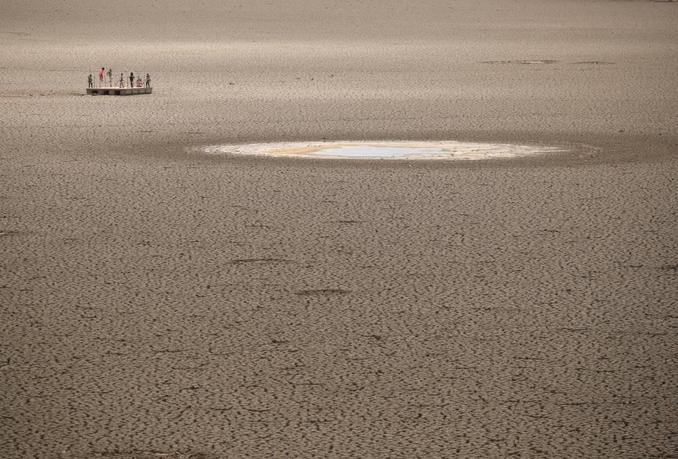 Crianças brincam em um açude seco na África do Sul.
