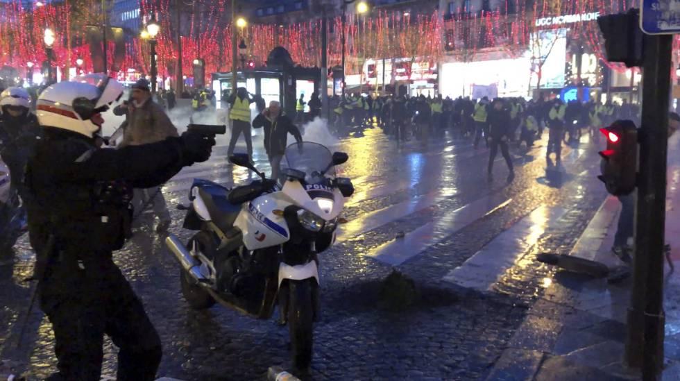 Policial tenta dispersar manifestantes na avenida Champs Elysées, em Paris