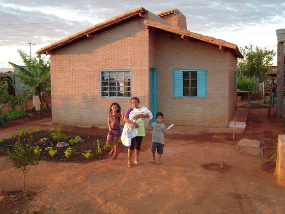Família em frente à casa construída pelo projeto Ação Moradia.