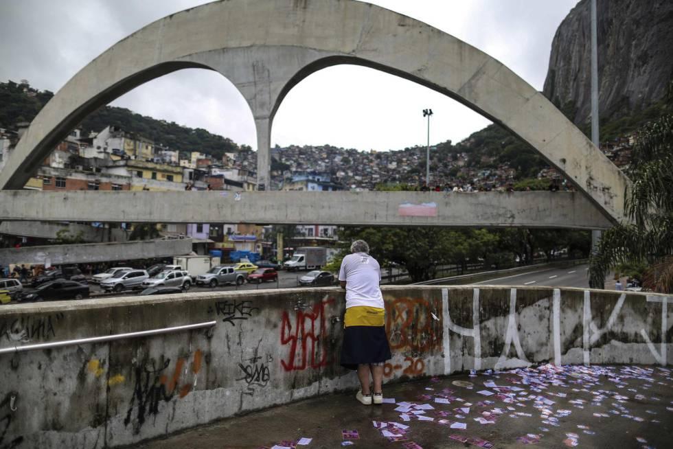 Vista da Rocinha, no Rio, no domingo: ao fundo, santinhos no chão e, ao fundo, a fila de eleitores aguardando para votar no primeiro turno.