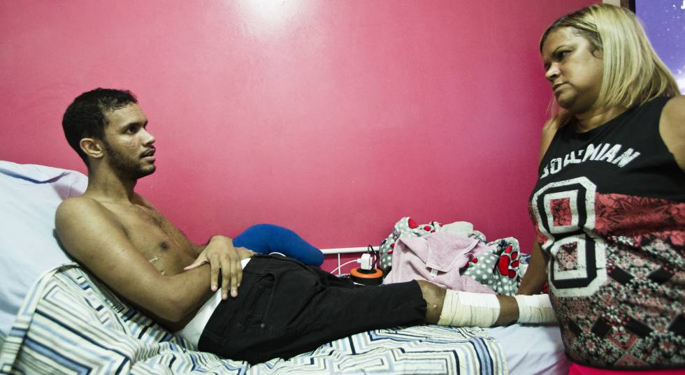 Vitor Santiago Borges, ferido pela polícia, com sua mãe no complexo da Maré.