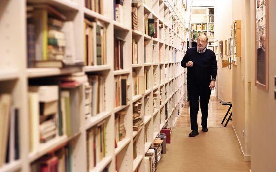 Umberto Eco caminha diante da estante de livros em sua casa.