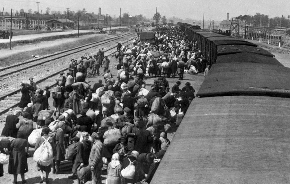 Chegada de deportados a Auschwitz. Ao fundo, as chaminés dos fornos crematórios.