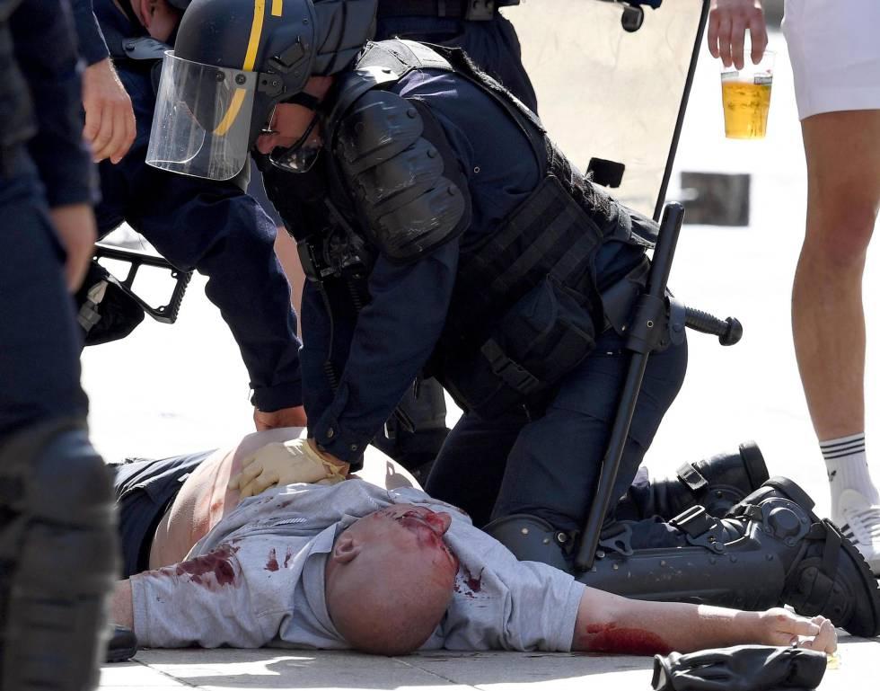Um policial atende um torcedor britânico ferido após o jogo Inglaterra-Rússia