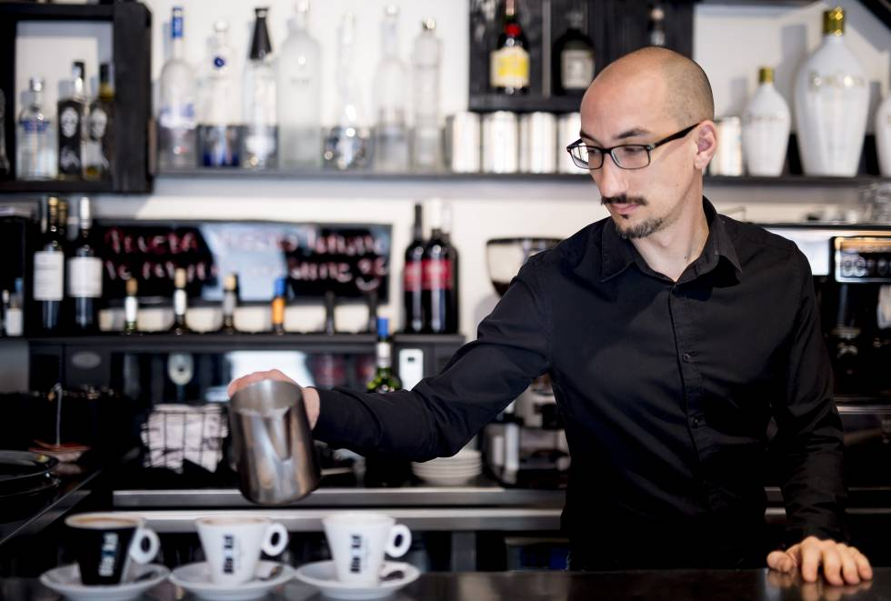 Um garçom prepara três cafés em um bar de Madri.