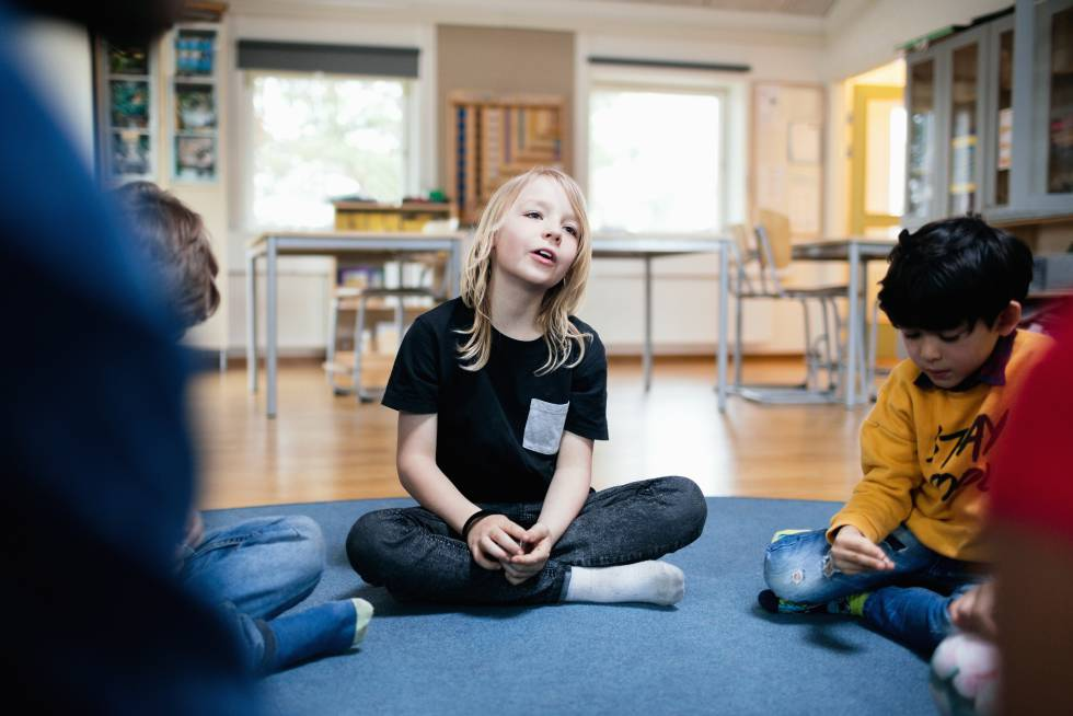 Várias crianças celebram uma assembleia na sala de aula.