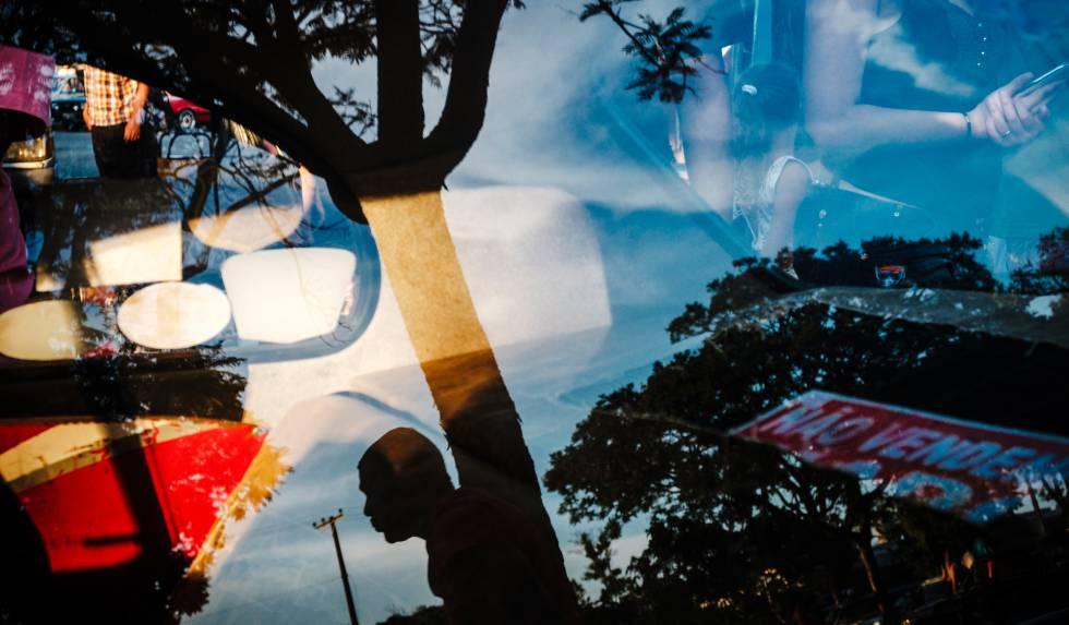 Homem refletido em vidro de carro em encontro do Clube do Opala. Brasília, 2017.