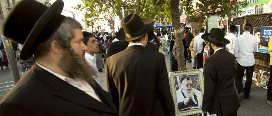 Judeus ultraortodoxos caminham ao lado de um retrato do líder espiritual já morto, o sefardita Ovadia Yosef, em outubro em Jerusalém.