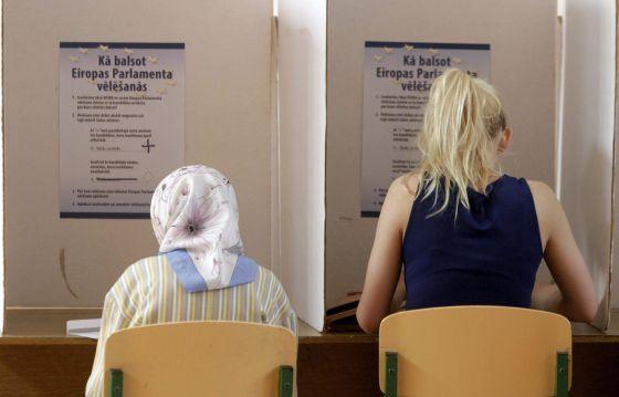Duas lituanas preenchem suas cédulas para as eleições europeias em Riga.