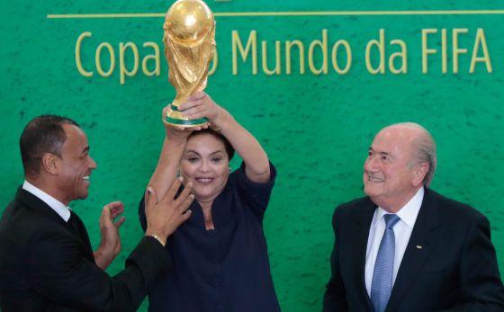 A presidenta Dilma Rousseff eleva o troféu ao lado do ex-jogador Cafu e de Joseph Blatter nesta segunda-feira.