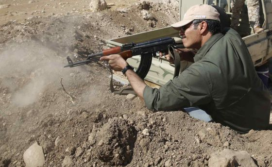 Um miliciano curdo dispara em direção a Baretle, cidade controlada pelo EI.