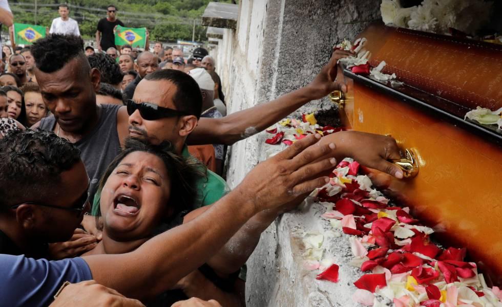 Luciana Nogueira, esposa de Evaldo Rosa dos Santos, no enterro do marido. Amigos do músico protestaram com bandeiras do Brasil manchadas de vermelho
