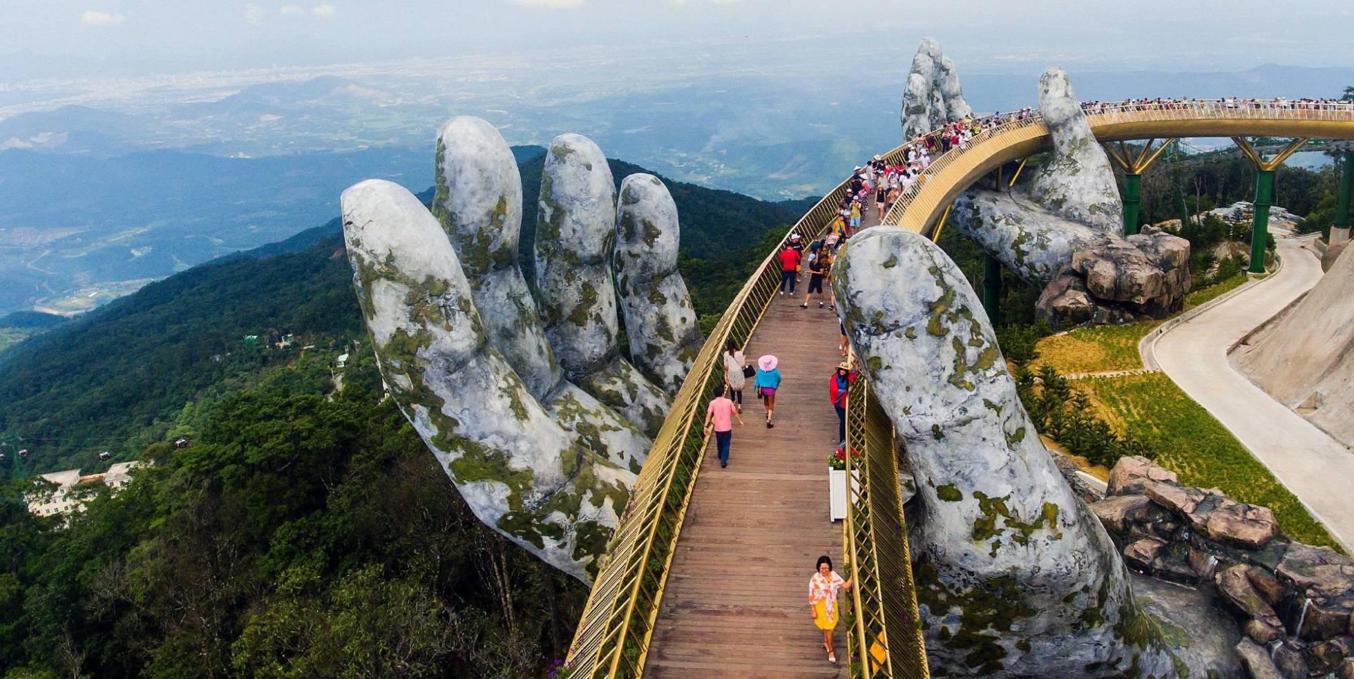 Varios turistas cruzan el nuevo puente Cau Vang (Puente Dorado).
