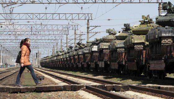 Uma mulher cruza uma via de trem junto a tanques ucranios carregados em plataformas para ser transladados desde Crimea a outras regiões.